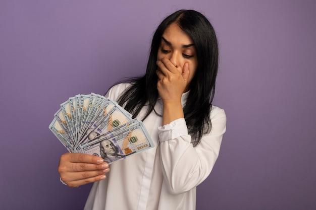 紫色で隔離の手で現金で覆われた口を保持し、見て白いtシャツを着て怖い若い美しい少女