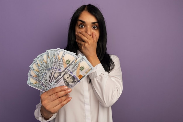 Испуганная молодая красивая девушка в белой футболке держит рот, покрытый деньгами, с рукой, изолированной на фиолетовом, с копией пространства