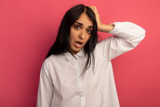 T-shirt bianca da portare della giovane bella ragazza spaventata che mette la mano sulla testa isolata sul colore rosa