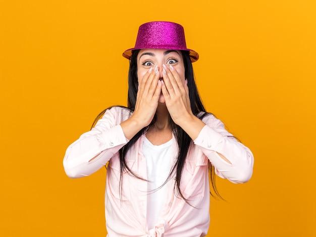 オレンジ色の壁に隔離された手でパーティーハットで覆われた顔を身に着けている怖い若い美しい女性