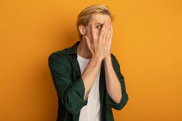 手で顔を覆われた緑のtシャツを着て怖い若いブロンドの男