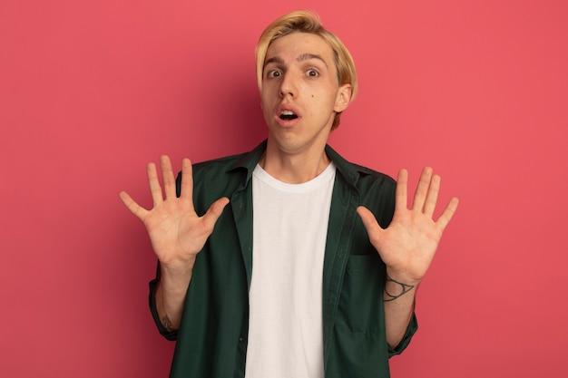 手を上げる緑のtシャツを着て怖い若いブロンドの男