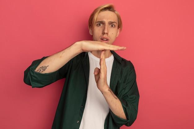 タイムアウトジェスチャーを示す緑のtシャツを着て怖い若いブロンドの男