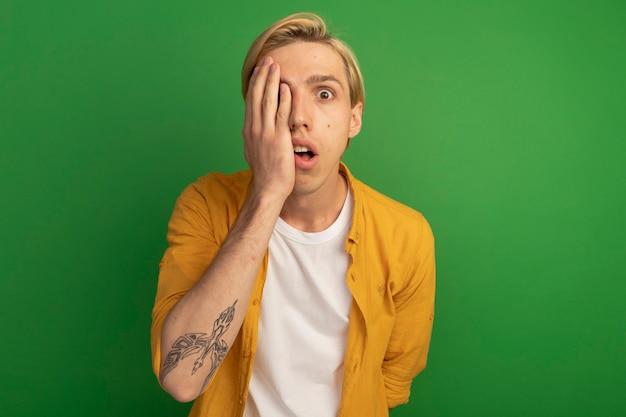 노란색 티셔츠를 입고 무서워 젊은 금발의 남자가 복사 공간이 녹색에 고립 된 손으로 얼굴을 덮여