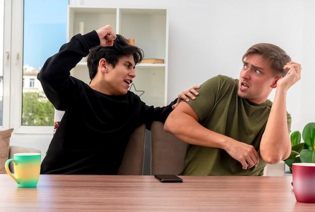 テーブルに座って、彼を打つ猛烈な若いブルネットのハンサムな男の子を見て手を上げる怖い若いブロンドのハンサムな男