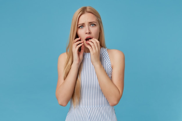 Scared young blonde lady with long hair frowning and covering with hands opened mouth, posing, looking with frightened face