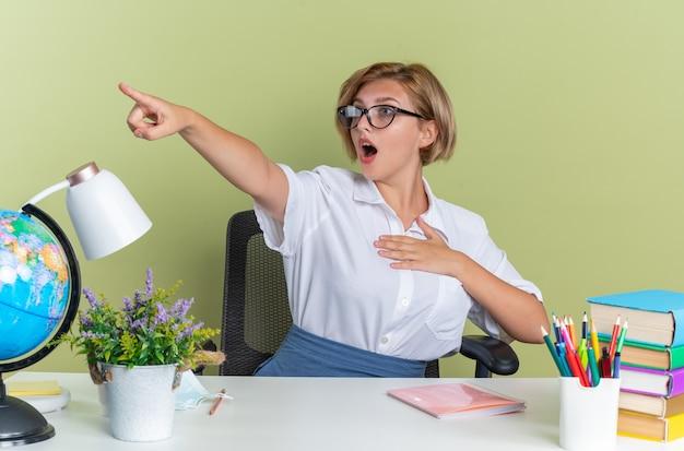 Giovane studentessa bionda spaventata con gli occhiali seduto alla scrivania con gli strumenti della scuola che tiene la mano sul petto guardando e indicando il lato isolato sul muro verde oliva