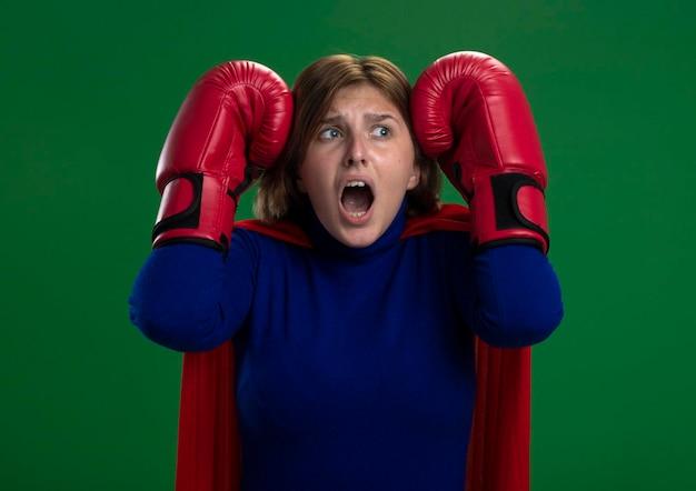 Spaventata giovane donna bionda supereroe in mantello rosso che indossa i guanti di scatola tenendo le mani sulla testa guardando il lato isolato sulla parete verde