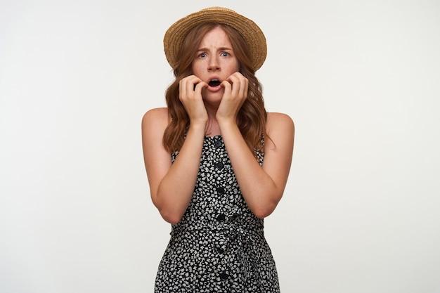 Spaventata giovane donna dagli occhi blu in cappello di paglia e abbigliamento casual guardando con la bocca spalancata, accigliato e tenendo le mani sulle guance, isolato