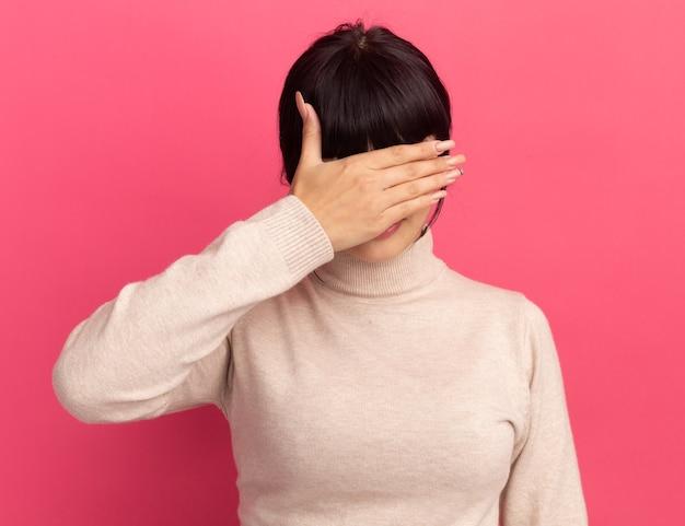 怖い若いブルネットの白人の女の子は手で顔をカバーします
