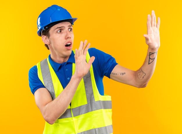 Испуганный молодой строитель в униформе, протягивая руки в стороне, изолированной на желтой стене
