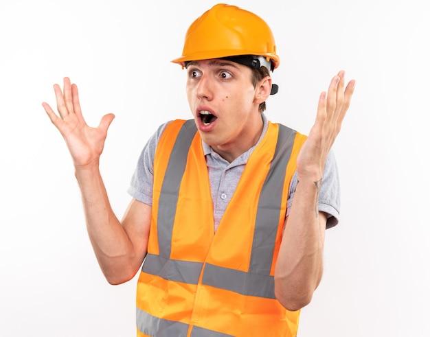 Испуганный молодой строитель в униформе, разводя руками, изолированными на белой стене