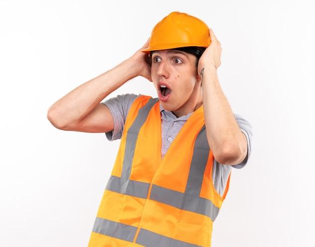 Il giovane muratore spaventato in uniforme ha afferrato la testa
