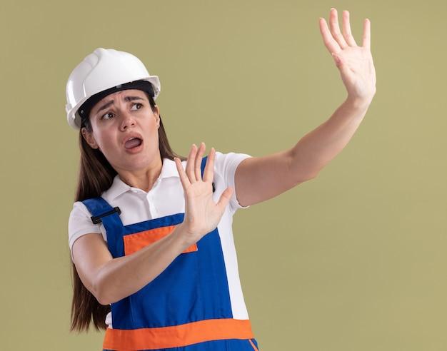 올리브 녹색 벽에 고립 된 손을 들고 제복을 입은 무서 워 젊은 작성기 여자