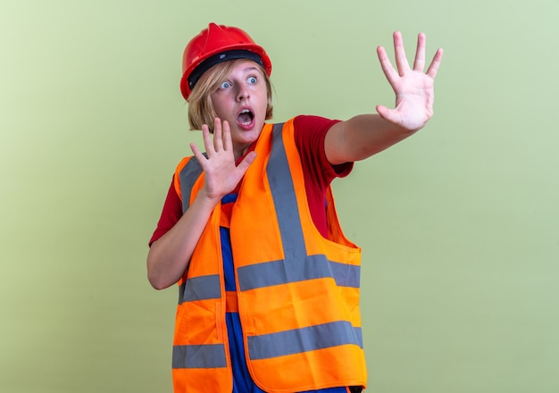 Spaventata giovane donna costruttore in uniforme che tende le mani a lato isolata sul muro verde oliva