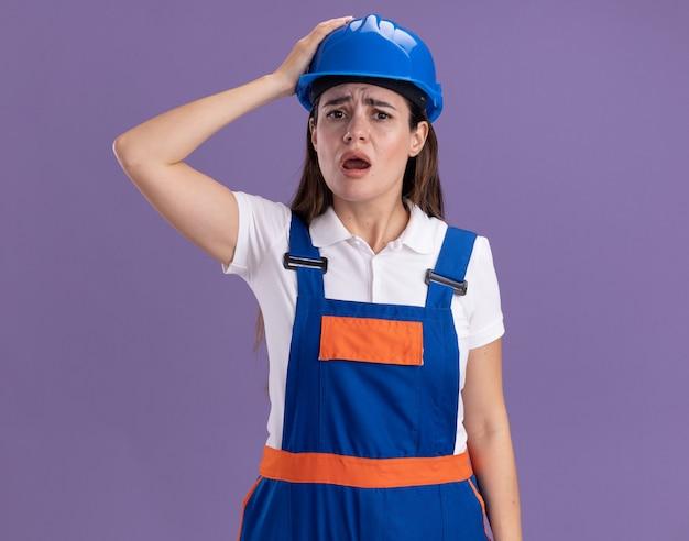 Giovane donna spaventata del costruttore in uniforme che mette mano sulla testa isolata sul muro viola