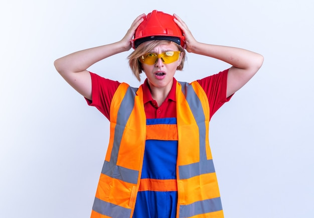 Scared young builder woman in uniform with glasses grabbed head isolated on white background