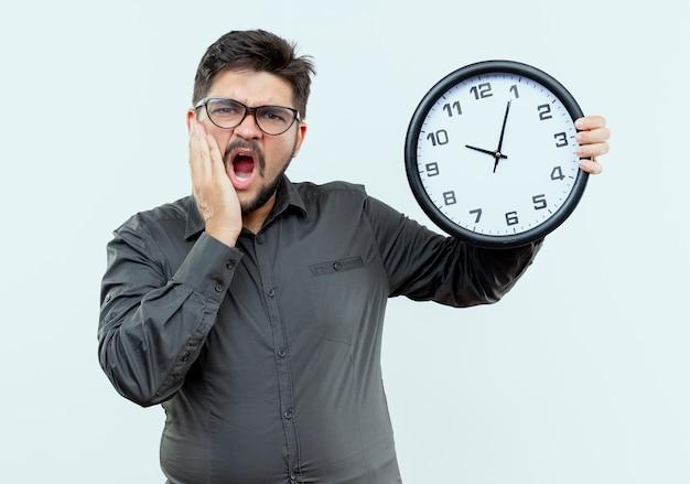 Spaventato giovane imprenditore con gli occhiali tenendo l'orologio da parete e mettendo la mano sulla guancia isolato su bianco