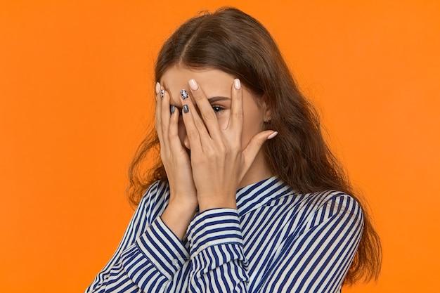 Испуганная молодая кавказская женщина прячет свой страх за руками.