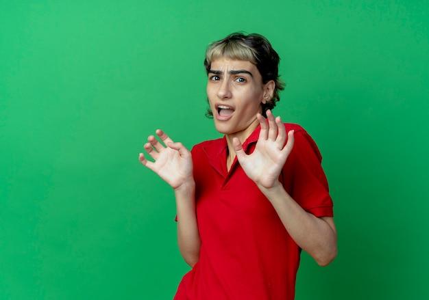 コピースペースで緑の背景に分離された空の手を示すピクシーヘアカットの怖い若い白人の女の子