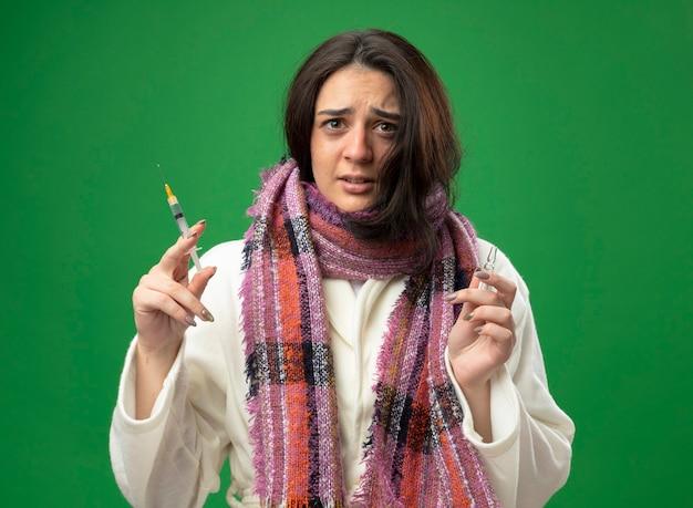 Spaventata giovane ragazza malata caucasica che indossa accappatoio e sciarpa tenendo la fiala e la siringa che guarda l'obbiettivo isolato su priorità bassa verde