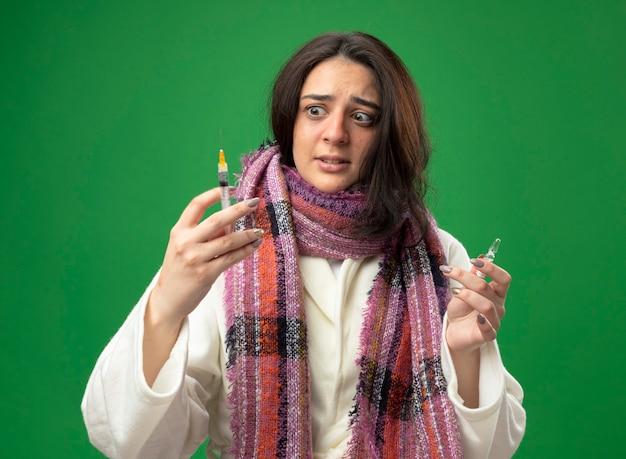 Spaventata giovane ragazza malata caucasica che indossa veste e sciarpa che tiene la fiala e la siringa guardando la siringa isolata sulla parete verde