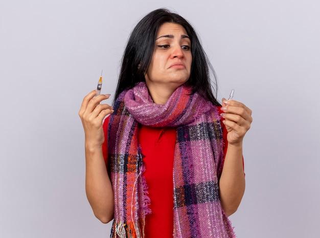 Sciarpa da portare della giovane ragazza ammalata caucasica spaventata che tiene la siringa e la fiala che esaminano la fiala isolata sulla parete bianca con lo spazio della copia