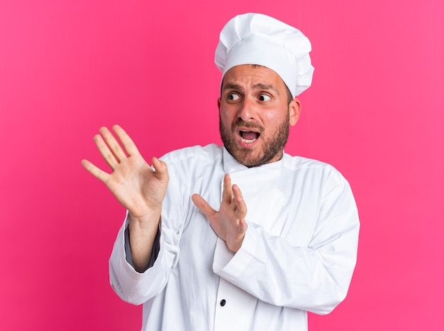 Spaventato giovane maschio caucasico cuoco in uniforme da chef e cappuccio guardando il lato facendo gesto di rifiuto