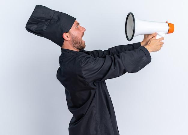 Испуганный молодой кавказский повар в униформе шеф-повара и кепке, стоящий в профиле, протягивается и смотрит на спикера, изолированного на белой стене