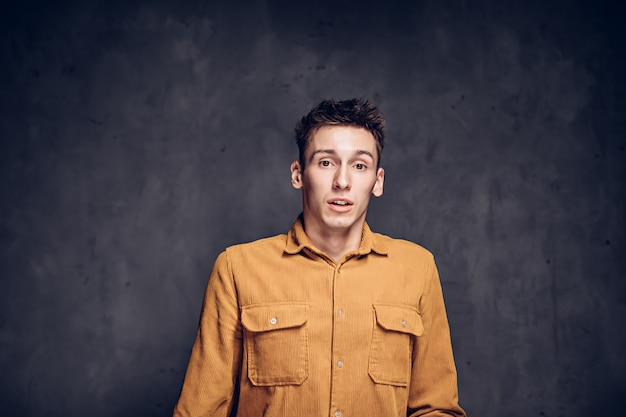 Scared young caucasian man on grey dark background