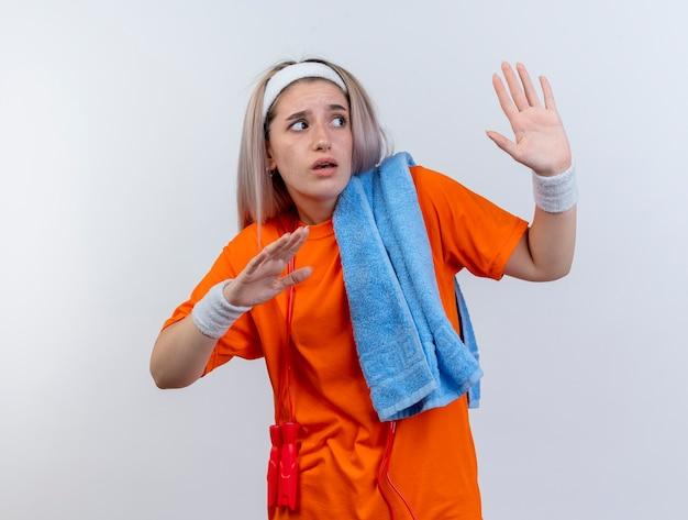 중괄호와 어깨에 수건을 들고 머리띠 팔찌를 착용 목 주위에 밧줄 점프 무서워 젊은 백인 스포티 한 소녀는 흰 벽에 고립 된 측면을보고 손을 올립니다