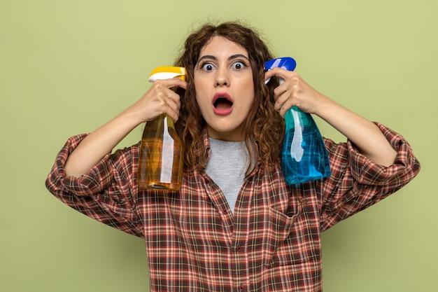 顔の周りに洗浄剤を保持している怖い若い洗浄女性