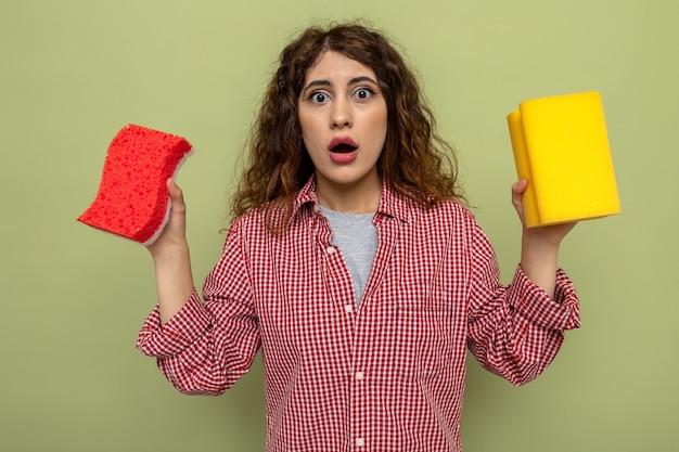 掃除用スポンジを持っている怖い若い掃除婦