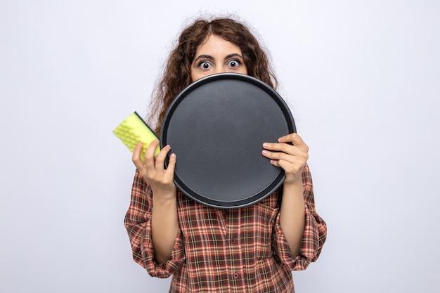 Giovane donna delle pulizie spaventata che tiene spugna e faccia coperta con vassoio isolato su parete bianca