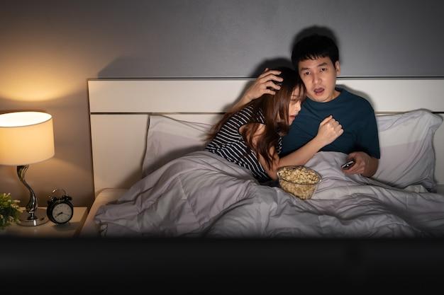 Испуганная молодая пара смотрит телевизор ужасов на кровати ночью