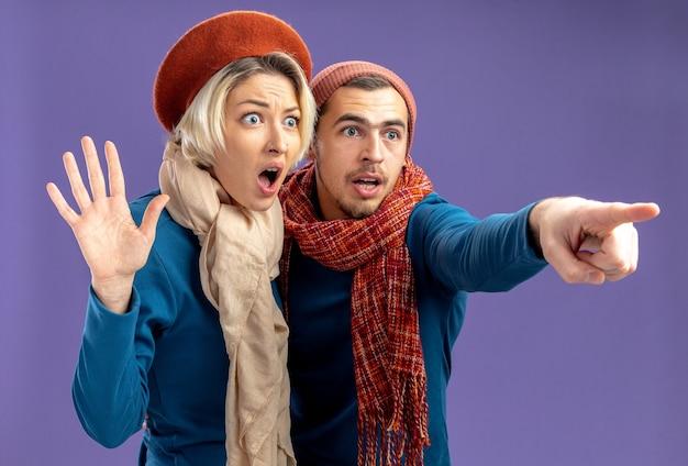 Giovane coppia spaventata che indossa un cappello con sciarpa il giorno di san valentino ragazza che allarga le mani ragazzo punta a lato isolato su sfondo blu