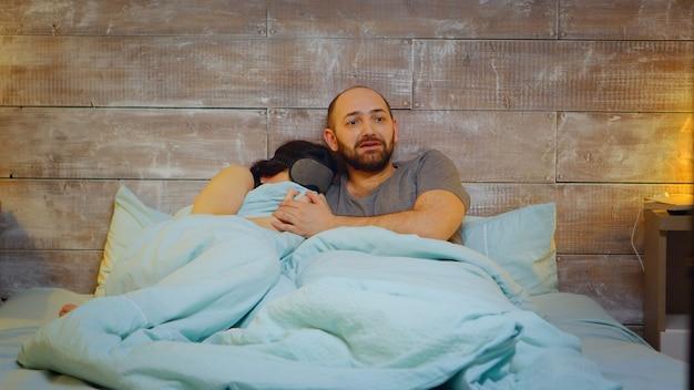 Испуганная молодая пара во время просмотра фильма ужасов по телевизору. пара в пижаме.