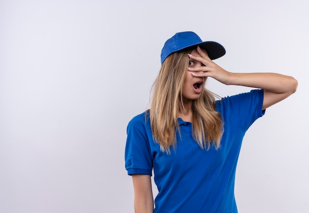 青い制服とキャップを身に着けている怖い若い配達の女の子は、コピースペースで白い壁に隔離された手で目を覆った