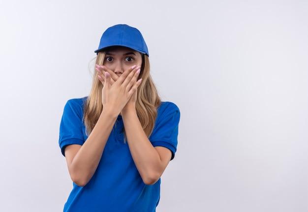 Giovane ragazza spaventata di consegna che indossa l'uniforme blu e la bocca coperta del cappuccio con le mani isolate su bianco