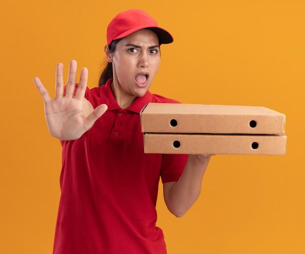 Испуганная молодая доставщица в униформе и кепке держит коробки для пиццы, показывая жест остановки, изолированный на оранжевой стене