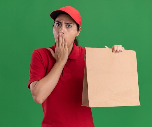 La giovane ragazza spaventata delle consegne che indossa l'uniforme e il cappuccio che tiene il pacchetto di cibo di carta ha coperto la bocca con la mano isolata sulla parete verde