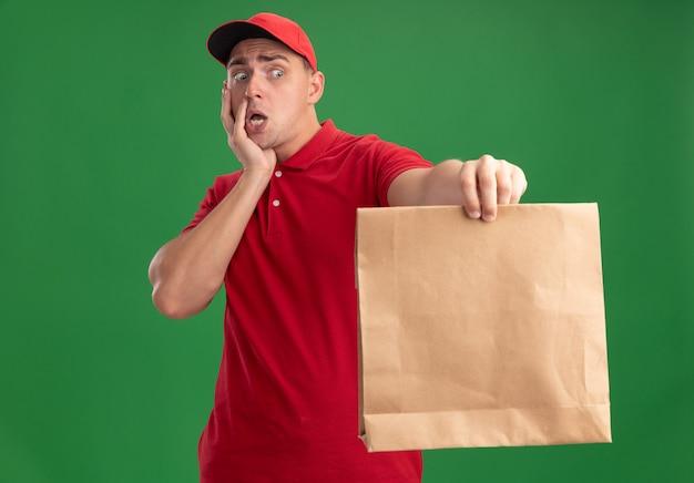 Giovane uomo di consegna spaventato che indossa l'uniforme e il cappuccio che tiene fuori il pacchetto di cibo di carta alla macchina fotografica che mette la mano sulla guancia isolata sulla parete verde