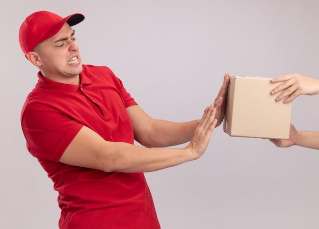 白い壁に隔離されたクライアントにボックスを与えるキャップと制服を着て怖い若い配達人