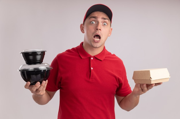 Giovane uomo di consegna spaventato che indossa l'uniforme con il cappuccio che tiene il pacchetto alimentare di carta con il contenitore per alimenti isolato sulla parete bianca