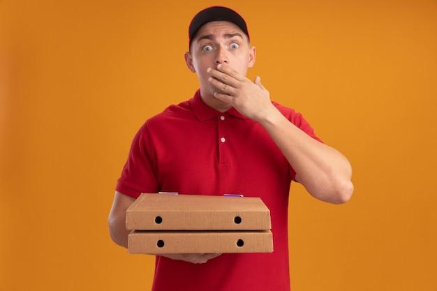Giovane uomo di consegna spaventato che indossa l'uniforme con cappuccio che tiene le scatole per pizza coperto la bocca con la mano isolata sulla parete arancione