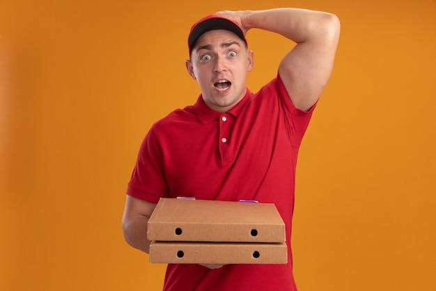 오렌지 벽에 고립 된 머리에 손을 넣어 피자 상자를 들고 모자와 유니폼을 입고 무서 워 젊은 배달 남자