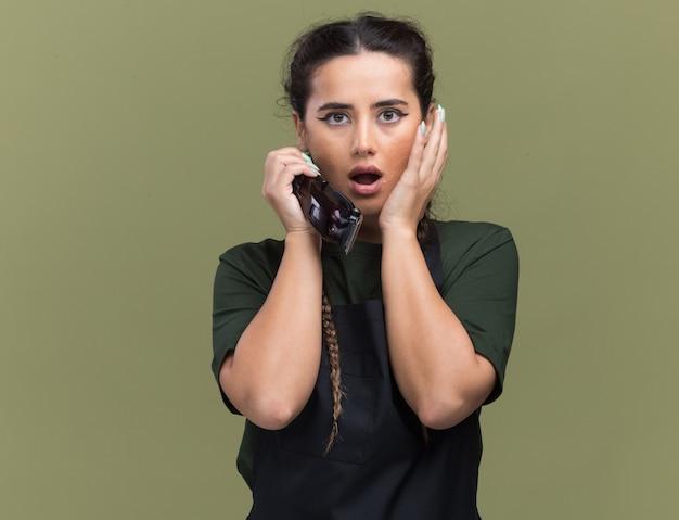 オリーブグリーンの壁に分離された頬に手を置くバリカンを保持している制服を着た若い女性の理髪師を怖がらせる