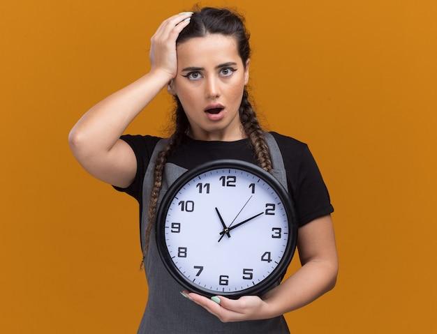 Spaventato giovane barbiere femminile in uniforme che tiene l'orologio da parete e mettendo la mano sulla testa isolata sulla parete arancione