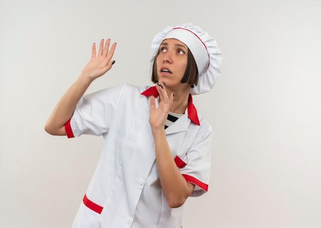 Giovane cuoco femminile spaventato in uniforme del cuoco unico che esamina lato con le mani alzate isolate sulla parete bianca