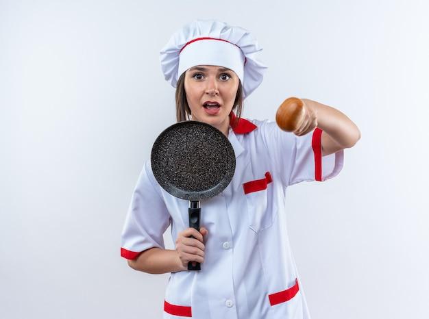 フライパンを保持し、白い背景で隔離のカメラでスプーンを差し出すシェフの制服を着て怖い若い女性料理人